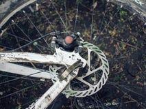 一辆肮脏的自行车在地面上说谎 细节是特写镜头,轮子从在恶劣天气的一次旅行是肮脏的 免版税库存图片