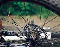 一辆肮脏的自行车在地面上说谎 细节是特写镜头,轮子从在恶劣天气的一次旅行是肮脏的 免版税图库摄影