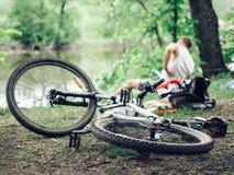 一辆肮脏的自行车在地面上说谎 细节是特写镜头,轮子从在恶劣天气的一次旅行是肮脏的 库存照片
