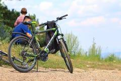 一辆自行车和两个人在山顶部 免版税库存图片