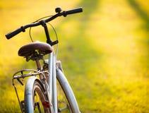 一辆自行车在日落期间的草甸 免版税库存照片