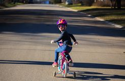 一辆自行车的一个时兴的小女孩有三轮车的 库存图片