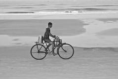 一辆自行车的一位年轻茶卖主在一个海滩在北部果阿 免版税库存图片