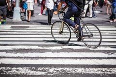 一辆自行车的人在横穿在曼哈顿 库存图片