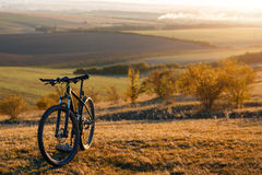 一辆自行车的剪影在小山的在日落 免版税库存照片