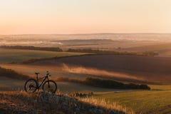 一辆自行车的剪影在小山的在日落 免版税库存图片