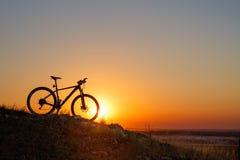 一辆自行车的剪影在小山的在日落 库存照片