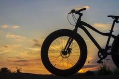 一辆自行车的剪影在日落的 库存照片