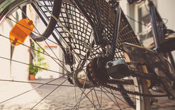 一辆自行车的后轮有橙色车灯的 一辆黑自行车站立在大厦附近在一热的天 库存图片
