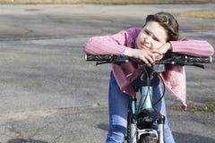 一辆自行车的女孩在一个城市环境里 查找周道 免版税图库摄影