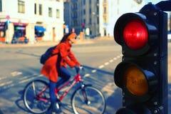 一辆自行车的女孩在一个红色红绿灯的一条城市街道上 免版税库存照片