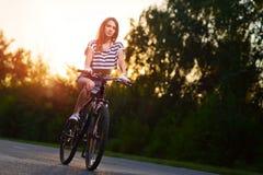一辆自行车的女孩在日落 免版税库存照片