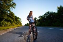 一辆自行车的女孩在日落 图库摄影