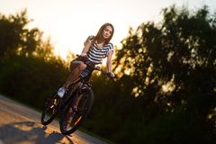一辆自行车的女孩在日落 免版税库存图片