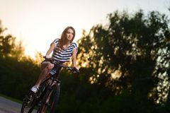 一辆自行车的女孩在日落 免版税图库摄影