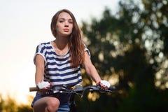 一辆自行车的女孩在日落 库存图片