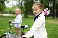 一辆自行车的女孩在绿色公园 库存图片