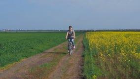 一辆自行车的女孩在自然 妇女骑在城市之外的一辆自行车 健康生活方式 油菜籽领域 航空蓝色云彩国家(地区)开放全景路西西里岛天空 股票视频