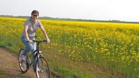 一辆自行车的女孩在自然 妇女骑在城市之外的一辆自行车 健康生活方式 油菜籽领域 航空蓝色云彩国家(地区)开放全景路西西里岛天空 股票录像
