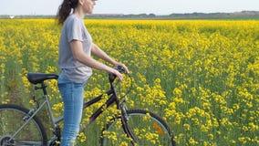 一辆自行车的女孩在自然 妇女骑在城市之外的一辆自行车 健康生活方式 油菜籽领域 航空蓝色云彩国家(地区)开放全景路西西里岛天空 影视素材