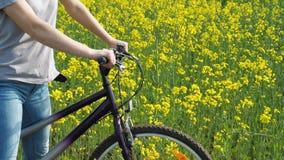 一辆自行车的女孩在自然 妇女骑在城市之外的一辆自行车 油菜籽领域 航空蓝色云彩国家(地区)开放全景路西西里岛天空 股票录像