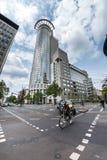 一辆自行车的妇女有高办公楼的在背景中 免版税库存图片