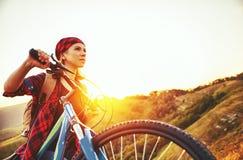 一辆自行车的妇女游人在户外日落的山顶部 免版税库存照片