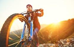 一辆自行车的妇女游人在户外日落的山顶部 库存图片