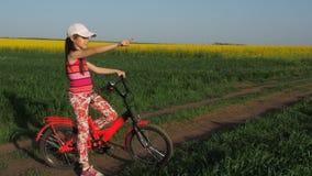 一辆自行车的孩子在乡下 领域的女孩在自行车 油菜籽领域 日域热夏天麦子 航空蓝色云彩国家(地区)开放全景路西西里岛天空 影视素材