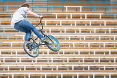 一辆自行车的少年在跳高 免版税库存照片