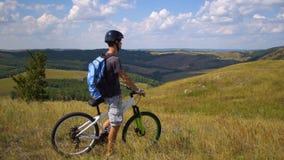 一辆自行车的年轻人在反对天空的青山中与云彩 库存照片