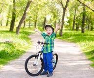 一辆自行车的快乐的小男孩在夏天公园 免版税库存图片