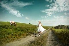 一辆自行车的愉快的妇女在乡下 库存图片