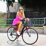 一辆自行车的愉快的微笑的女孩在夏天 免版税库存照片