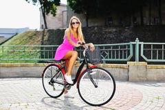 一辆自行车的愉快的微笑的少妇在夏天 库存图片