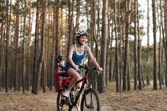 一辆自行车的愉快的母亲有后边小儿子的 库存图片