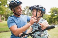 一辆自行车的愉快的父亲有他的儿子的 库存图片