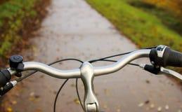 一辆自行车的方向盘有道路的在背景中 库存图片
