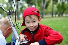 一辆自行车的男孩在绿色公园 库存图片