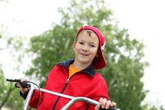 一辆自行车的男孩在绿色公园 免版税库存照片