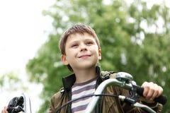 一辆自行车的男孩在绿色公园 图库摄影