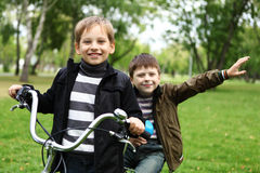 一辆自行车的男孩在绿色公园 免版税库存图片