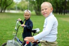一辆自行车的男孩在绿色公园 免版税图库摄影