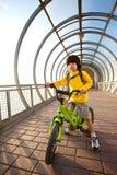 一辆自行车的男孩在被遮盖的桥 免版税图库摄影