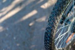 一辆自行车的轮子在路背景的 库存图片