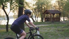 一辆自行车的适合的嬉戏女性骑自行车者在日落前的城市公园 r 股票录像