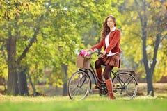 一辆自行车的年轻女性在公园 免版税库存照片