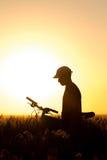 一辆自行车的年轻男孩在领域 免版税库存照片