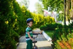 一辆自行车的画象微笑的孩子男孩在柏油路在公园 免版税库存图片