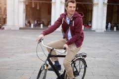 一辆英俊的微笑的人骑马自行车的照片在城市 免版税库存照片